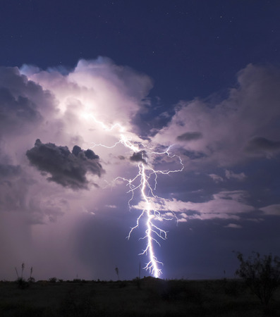 A Bolt of Lightning Strikes in a Stormy Desert Night and Seems to Hit a Housetop Foto de archivo