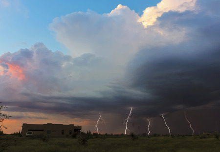 monsoon clouds: A Dance of Five Lightning Strikes as the Sun Sets Stock Photo