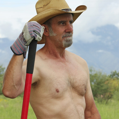 rancher: A Shirtless Rancher in a Straw Cowboy Hat Pauses While Working on His Ranch