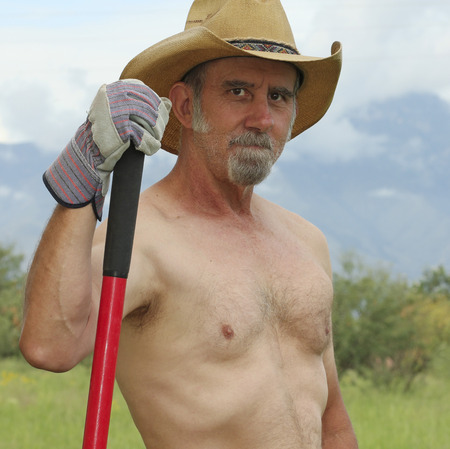 working cowboy: A Shirtless Rancher in a Straw Cowboy Hat Pauses While Working on His Ranch