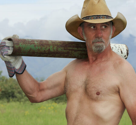 rancher: A Shirtless Rancher in a Straw Cowboy Hat Shoulders a Fence Post Driver on His Ranch Stock Photo