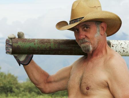 nackte brust: Ein Nackter Oberkörper Rancher in einem Stroh-Cowboyhut Schultern einem Zaunpfosten Treiber auf seiner Ranch