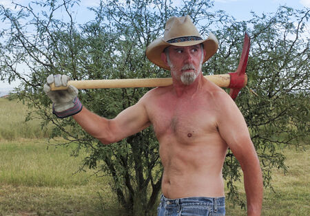sideburns: A Shirtless Rancher in a Straw Cowboy Hat Shoulders a Red Pickax on His Ranch Stock Photo