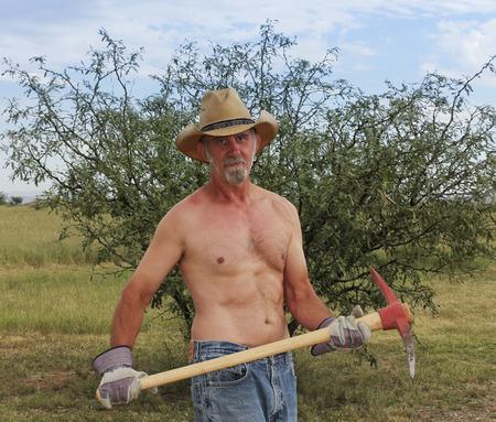 nackte brust: Ein Nackter Oberkörper Rancher in einem Stroh-Cowboyhut verwendet einen roten Pickax auf seiner Ranch