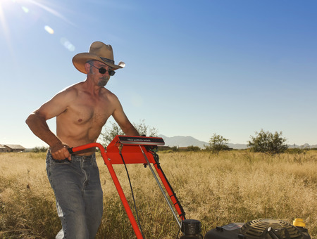 mows: A Shirtless Rancher in a Straw Cowboy Hat Operates a Field and Brush Mower on His Ranch