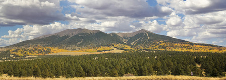 mount humphreys: A Woman is Dwarfed by the Spectacular San Francisco Peaks Panorama in Fall