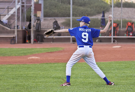 Las Vegas, Nevada - October 18: A Summerlin park on October 18, 2014, in Las Vegas, Nevada. A player  prepares to throw the ball in a youth baseball game in a Summerlin park in Las Vegas, Nevada.