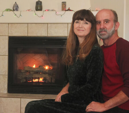 mantle: A Married Couple Sit in Front of a Fireplace at Christmas