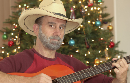 graying: A Cowboy with a Gray Beard Plays a Guitar in Front of a Christmas Tree