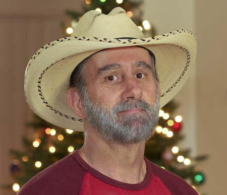 graying: A Cowboy with a Gray Beard in Front of a Christmas Tree
