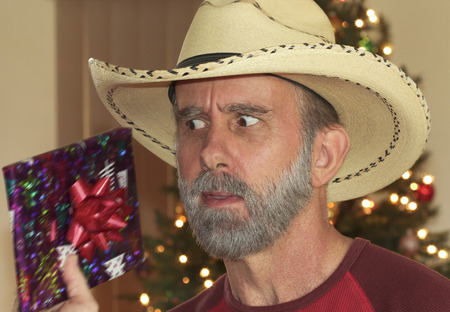 guess: A Cowboy with a Gray Beard in Front of a Christmas Tree Tries to Guess His Present by Shaking It Stock Photo