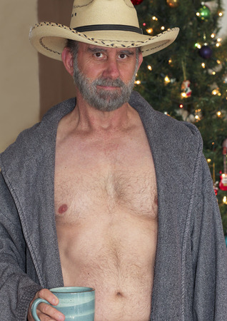 A Cowboy with a Gray Beard in an Open Robe in Front of a Christmas Tree
