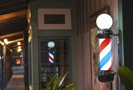 A Glowing Barber Pole on a Barbershop Porch at Night Stock Photo
