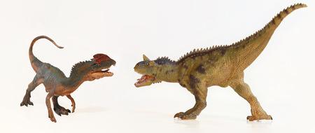 face off: A Dilophosaurus and a Carnotaurus Dinosaur Face Off in Battle Stock Photo