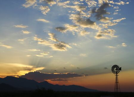 As the sun sets over the Huachuca Mountains in southeastern Arizona, a lonesome windmill is silhouetted against the striated sky. Imagens