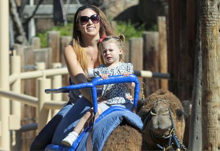 tucson: Tucson, Arizona - February 17: The Reid Park Zoo on February 17, 2015, in Tucson, Arizona. A mother and daughter take a camel ride at the Reid Park Zoo in Tucson, Arizona.