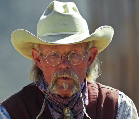 gunfights: Tucson, Arizona - March 9: Old Tucson on March 9, 2015, in Tucson, Arizona. An Old Tucson participant dressed in cowboy period costume welcomes tourists to historic Old Tucson  where gunfights and barroom brawls are staged in a celebration of the Old West