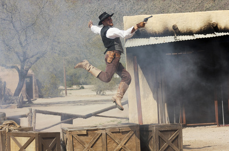 six shooter: Tucson, Arizona - March 9: Old Tucson on March 9, 2015, in Tucson, Arizona. An Old Tucson stuntman dressed in period cowboy costume thrills tourists at historic Old Tucson  where gunfights and barroom brawls are staged in a celebration of the Old West.