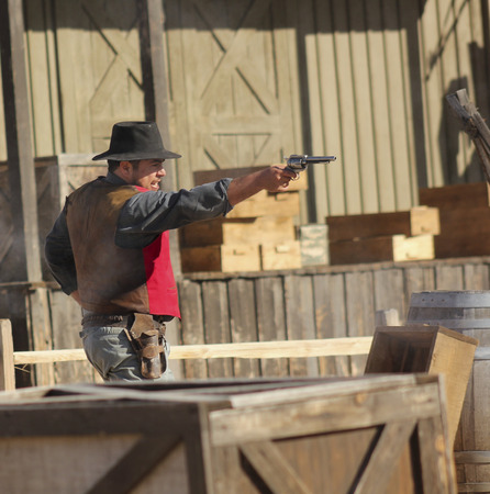 gunfights: Tucson, Arizona - March 9: Old Tucson on March 9, 2015, in Tucson, Arizona. An Old Tucson participant dressed in period cowboy costume thrills tourists at historic Old Tucson  where gunfights and barroom brawls are staged in a celebration of the Old West.