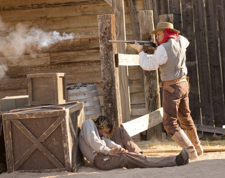 gunfighter: Tucson, Arizona - March 9: Old Tucson on March 9, 2015, in Tucson, Arizona. Old Tucson participants dressed in period cowboy costume thrill tourists at historic Old Tucson  where gunfights and barroom brawls are staged in a celebration of the Old West.