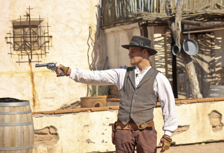 45 pistol: Tucson, Arizona - March 9: Old Tucson on March 9, 2015, in Tucson, Arizona. An Old Tucson participant dressed in period cowboy costume thrills tourists at historic Old Tucson  where gunfights and barroom brawls are staged in a celebration of the Old West.