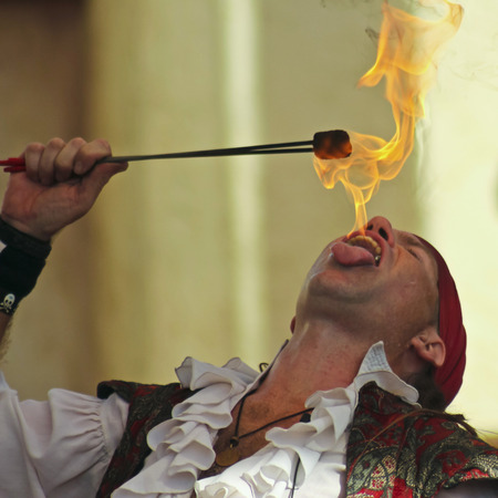 comedic: Apache Junction, Arizona - March 14: The Arizona Renaissance Festival on March 14, 2015, near Apache Junction, Arizona. A fire-eater thrills visitors in a pirate comedy show at the 27th Annual Arizona Renaissance Festival held near Phoenix.