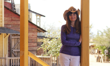western town: A Beautiful Brunette Cowgirl Leans Against a Porch Post in an Old Western Town