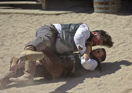 gunfights: Tucson, Arizona - March 9: Old Tucson on March 9, 2015, in Tucson, Arizona. A pair of stuntmen dressed in period costume welcome tourists to historic Old Tucson where gunfights and barroom brawls are staged in a celebration of the Old West.