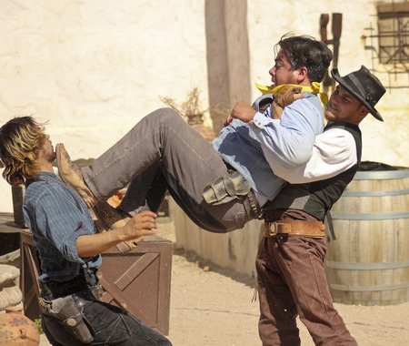 gunfights: Tucson, Arizona - March 9: Old Tucson on March 9, 2015, in Tucson, Arizona. A trio of stuntmen dressed in period costume welcome tourists to historic Old Tucson where gunfights and barroom brawls are staged in a celebration of the Old West.