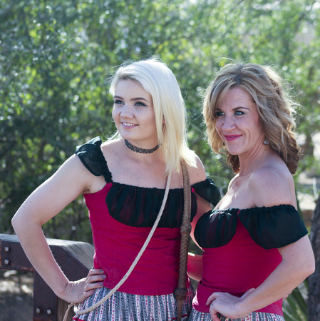 gunfights: Tucson, Arizona - March 9: Old Tucson on March 9, 2015, in Tucson, Arizona. A pair of saloon girls dressed in period costume welcome tourists to historic Old Tucson  where gunfights and barroom brawls are staged in a celebration of the Old West.