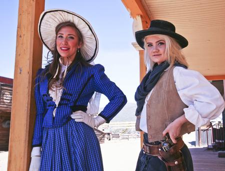 vestidos de epoca: Tucson, Arizona - 09 de marzo: Old Tucson el 9 de marzo de 2015, en Tucson, Arizona. Un par de mujeres fronterizas vestidos con traje de época turistas de bienvenida a la histórica Old Tucson, donde los tiroteos y peleas de bar se celebran en una celebración del viejo oeste. Editorial