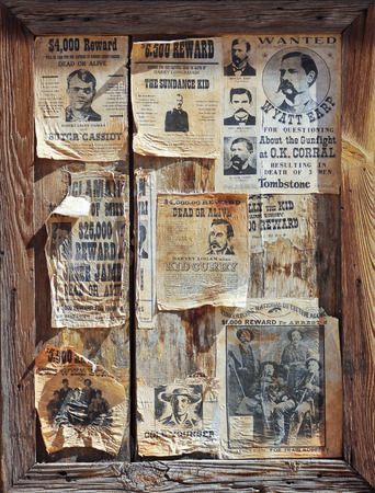 notorious: A weathered wooden frame full of assorted wanted posters of notorious outlaws of the Old West.