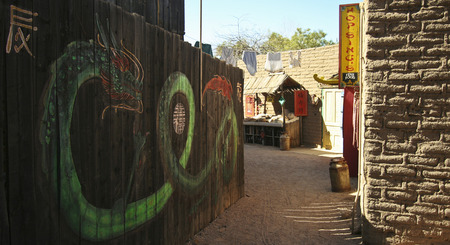 gunfights: Tucson, Arizona - March 9: Old Tucson on March 9, 2015, in Tucson, Arizona. An entrance to Chinatown welcomes tourists to historic Old Tucson  where gunfights and barroom brawls are staged in a celebration of the Old West.
