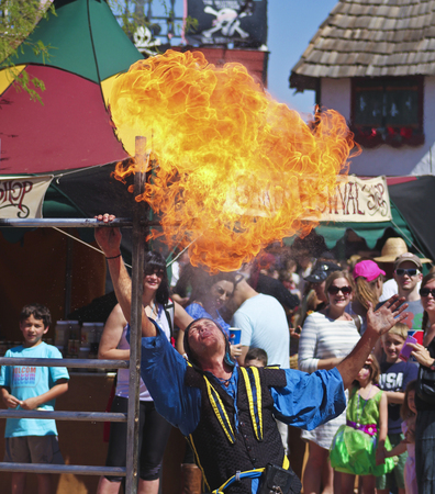 thrilling: Apache Junction, Arizona - March 14: The Arizona Renaissance Festival on March 14, 2015, near Apache Junction, Arizona. A fire juggler spits fire thrilling visitors in a show at the 27th Annual Arizona Renaissance Festival held near Phoenix.