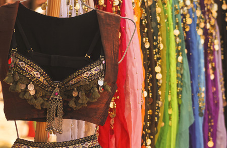 belly dance: A Belly Dance Costume Hangs in Front of an Assortment of Colorful Skirts
