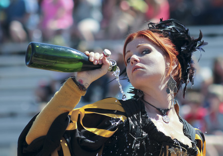 wench: Apache Junction, Arizona - March 14: The Arizona Renaissance Festival on March 14, 2015, near Apache Junction, Arizona. A red haired wench entertains visitors in a comedy show at the 27th Annual Arizona Renaissance Festival joust held near Phoenix.
