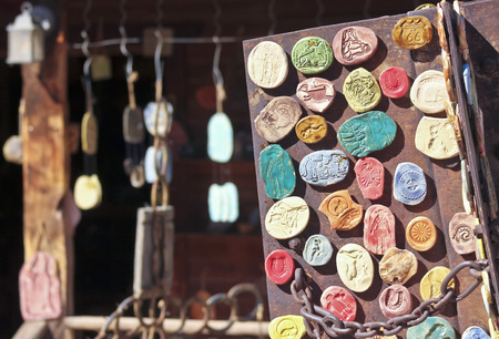 A Display of Rustic Clay Refrigerator Magnets and Wind Chimes