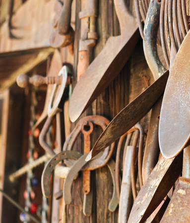 prongs: An Assortment of Rusty Tools Hangs from a Rustic Wooden Wall Stock Photo