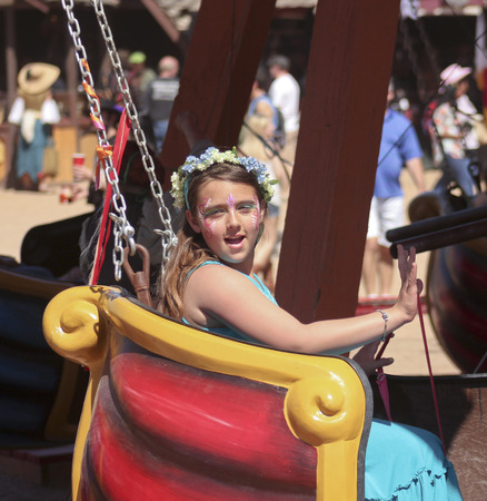 apache: APACHE JUNCTION, ARIZONA - MARCH 14: The Arizona Renaissance Festival on March 14, 2015, near Apache Junction, Arizona. A girl with face paint on a ride at the 27th Annual Arizona Renaissance Festival held near Phoenix.