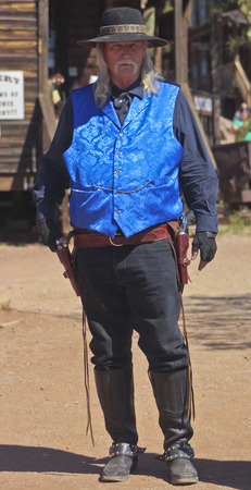 45 pistol: APACHE JUNCTION, ARIZONA - MARCH 15: Goldfield Ghost Town on March 15, 2015, near Apache Junction, Arizona. A gunfighter dressed in blue at Golfield Ghost Town near Apache Junction in Arizona.