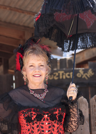 apache: APACHE JUNCTION, ARIZONA - MARCH 15: Goldfield Ghost Town on March 15, 2015, near Apache Junction, Arizona. A lady in red greets visitors to Goldfield Ghost Town near Apache Junction.