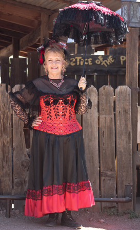 union familiar: Apache Junction, Arizona - 15 de marzo: Goldfield Ghost Town el 15 de marzo de 2015, cerca de Apache Junction, Arizona. Una señora en rojo recibe a los visitantes a Goldfield Ghost Town, cerca de Apache Junction. Editorial