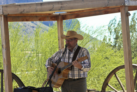 apache: APACHE JUNCTION, ARIZONA - MARCH 15: Goldfield Ghost Town on March 15, 2015, near Apache Junction, Arizona. Lee Alexander performs at the Mammoth Saloon at Goldfield Ghost Town in Arizona. Editorial