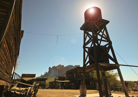 blazes: APACHE JUNCTION, ARIZONA - MARCH 15: Goldfield Ghost Town on March 15, 2015, near Apache Junction, Arizona. The morning sun blazes through an old water tower at Goldfield Ghost Town in Arizona.