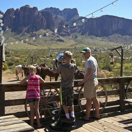 union familiar: Apache Junction, Arizona - 15 de marzo: Goldfield Ghost Town el 15 de marzo de 2015, cerca de Apache Junction, Arizona. Un ni�o mira a trav�s de un telescopio en las monta�as de la superstici�n en Goldfield Ghost Town en Arizona.