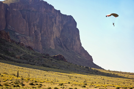 tonto national forest: A Pilot Paraglides Off of Flatiron in the Tonto National Forest and Superstition Mountain Wilderness in Lost Dutchman State Park, Arizona.