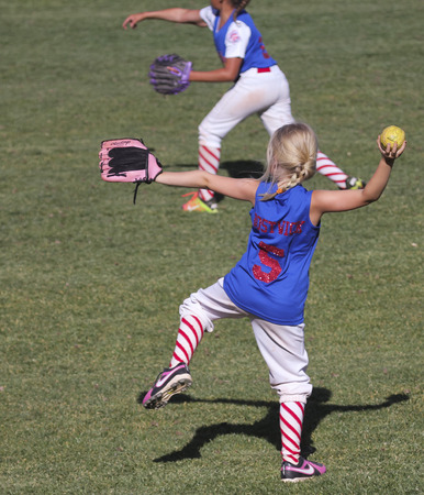 little league: SUMMERLIN, NEVADA - JUNE 4: A Summerlin Little League girls game on June 4, 2015, in Summerlin, Nevada. Two players warm up at a Summerlin Little League game in Summerlin in Nevada.