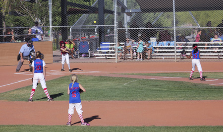 baseman: SUMMERLIN NEVADA  JUNE 4: A Summerlin Little League girls game on June 4 2015 in Summerlin Nevada. The batter hits the ball in a Summerlin Little League game in Summerlin in Nevada.