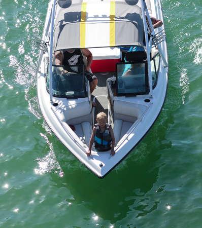 LAKE HAVASU CITY, ARIZONA - JUNE 6: Bridgewater Channel on June 6, 2015, in Lake Havasu City, Arizona. The boy stands in the prow of a boat, London Bridge, Bridgewater Channel, Lake Havasu City, Arizona.