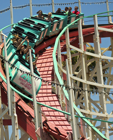 thrill: SAN DIEGO, CALIFORNIA, JUNE 23. Belmont Park on June 23, 2015, in San Diego, California. Thrill seekers ride the Giant Dipper roller coaster in Belmont Park in San Diego.